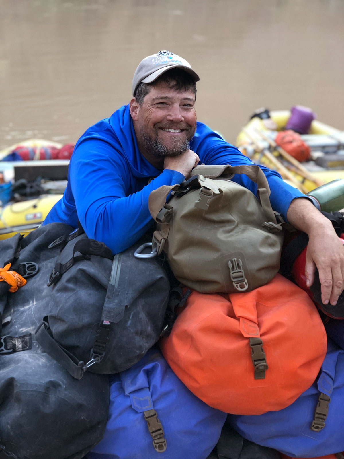 """Colorado river boatman John """"Bugs"""" Buggenhagen takes a moment to relax and a stack of Watershed of dry bags. © Adam Schallau..."""