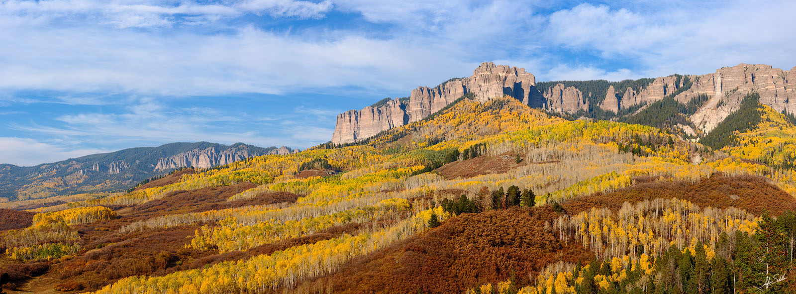 A panoramic view of fall color, courtest of aspen trees and scrub oaks, below the towering cliffs of Cimarron Ridge along the...