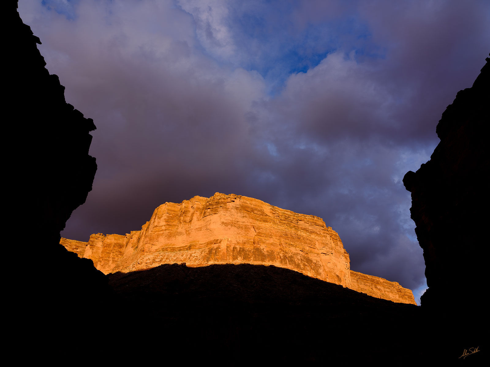 Dramatic light strikes the cliffs of Marble Canyon as a storm clears turning the rock to gold. From North Canyon in Grand Canyon...