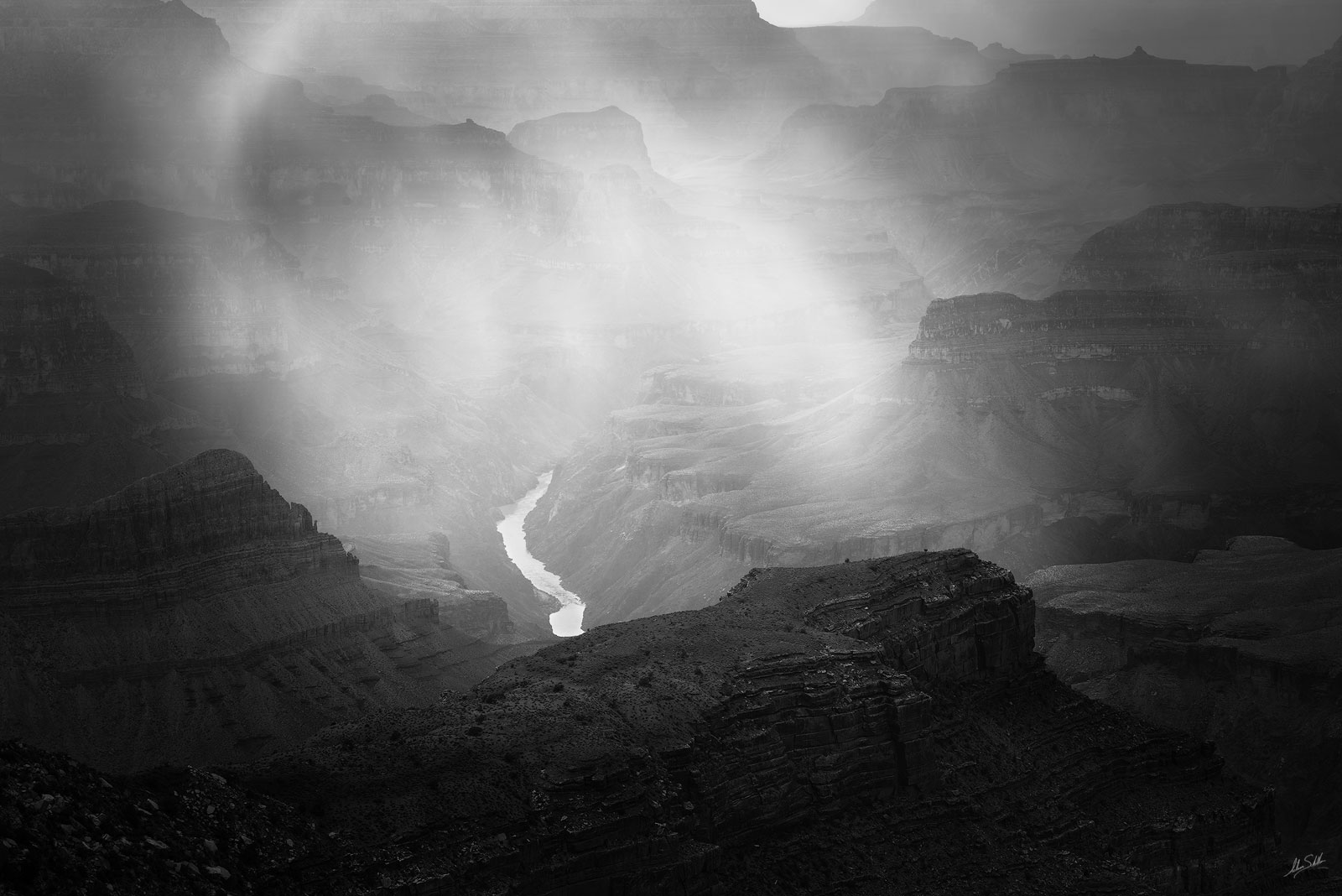 The Colorado River shimmers as sunlight streams through a light rain shower. From the South Rim of Grand Canyon National Park...