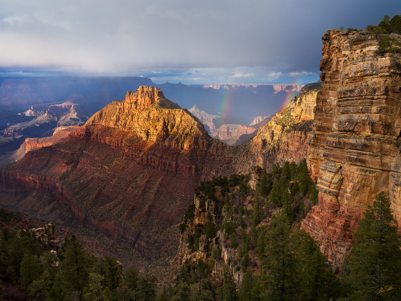 Double rainbows appear as a storm moves across the Grand Canyon. The large feature in the canyon is Coronado Butte, which is...