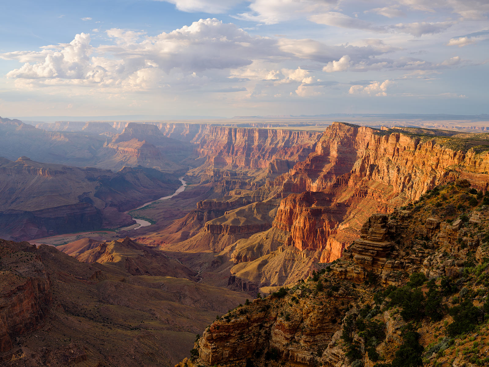 The sky above Grand Canyon and Palisades of the Desert fills with beautiful clouds as the Colorado River meanders far below....