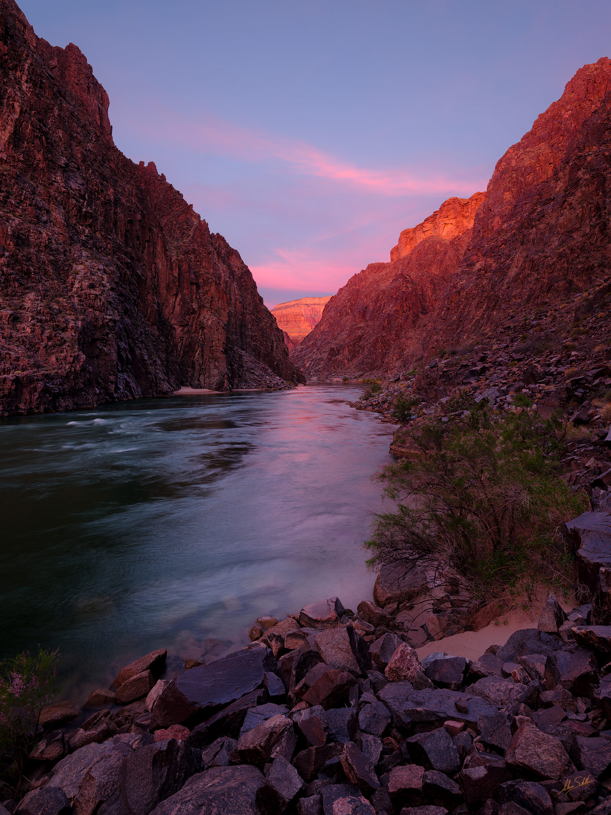 First light begins to paint distant cliffs in warm rosy hues. From Trinity Creek along the Colorado River deep within the Granite...