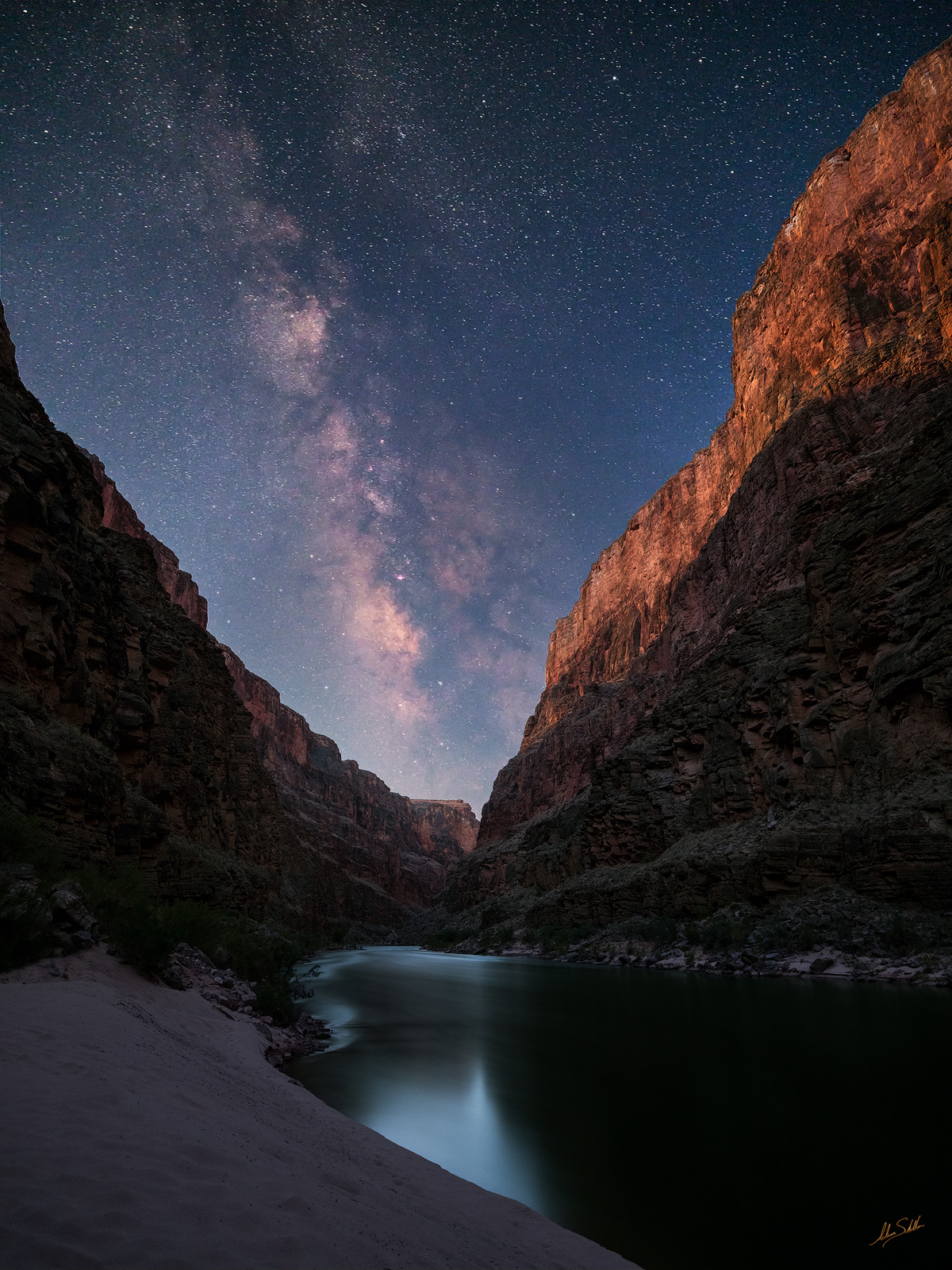 The towering cliffs of the Grand Canyon frame the Milky Way. A touch of moonlight illuminates the surrounding cliffs, and the...