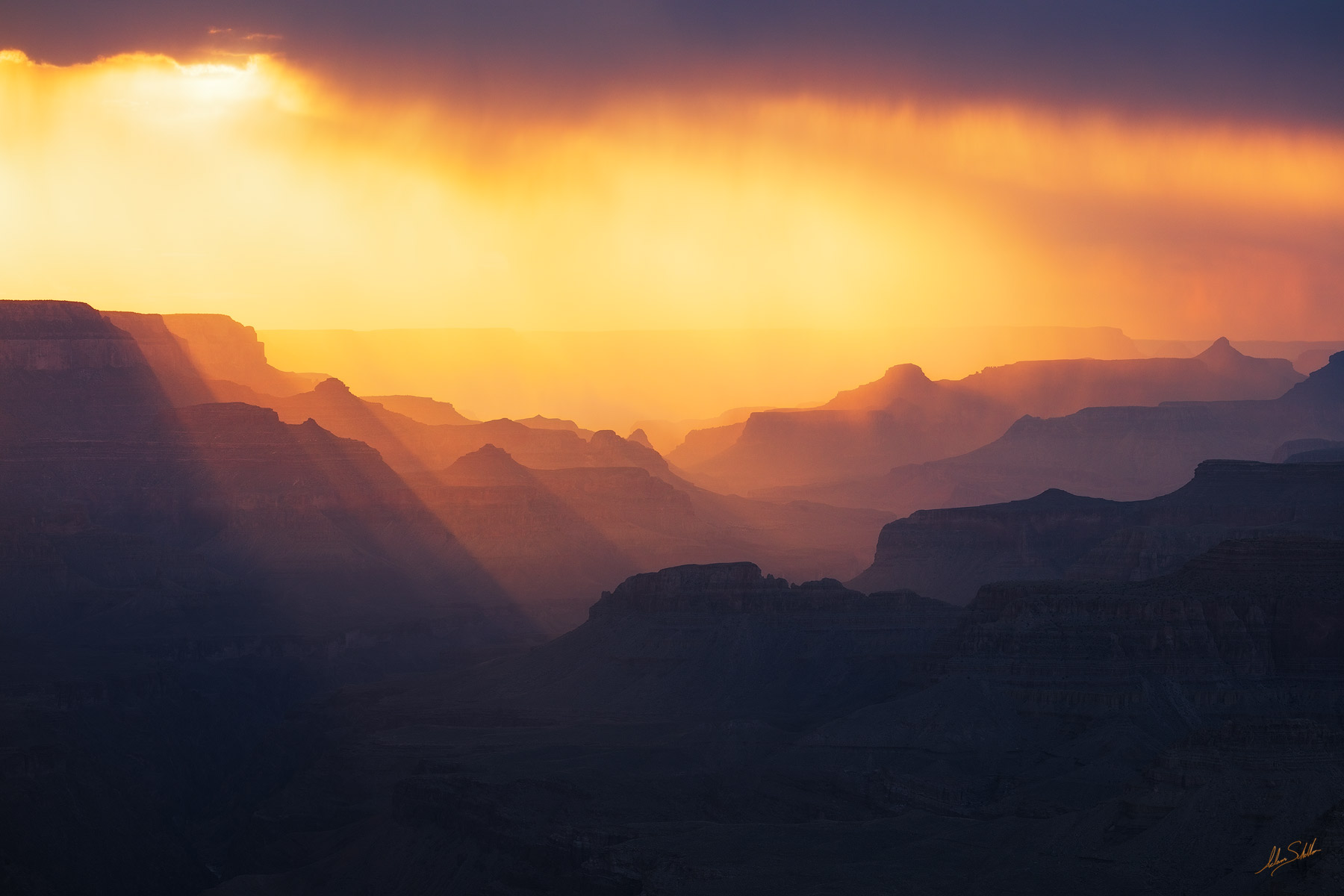 Summer rain is backlit by the setting sun as a monsoon storm begins to clear. From the South Rim of Grand Canyon National Park...