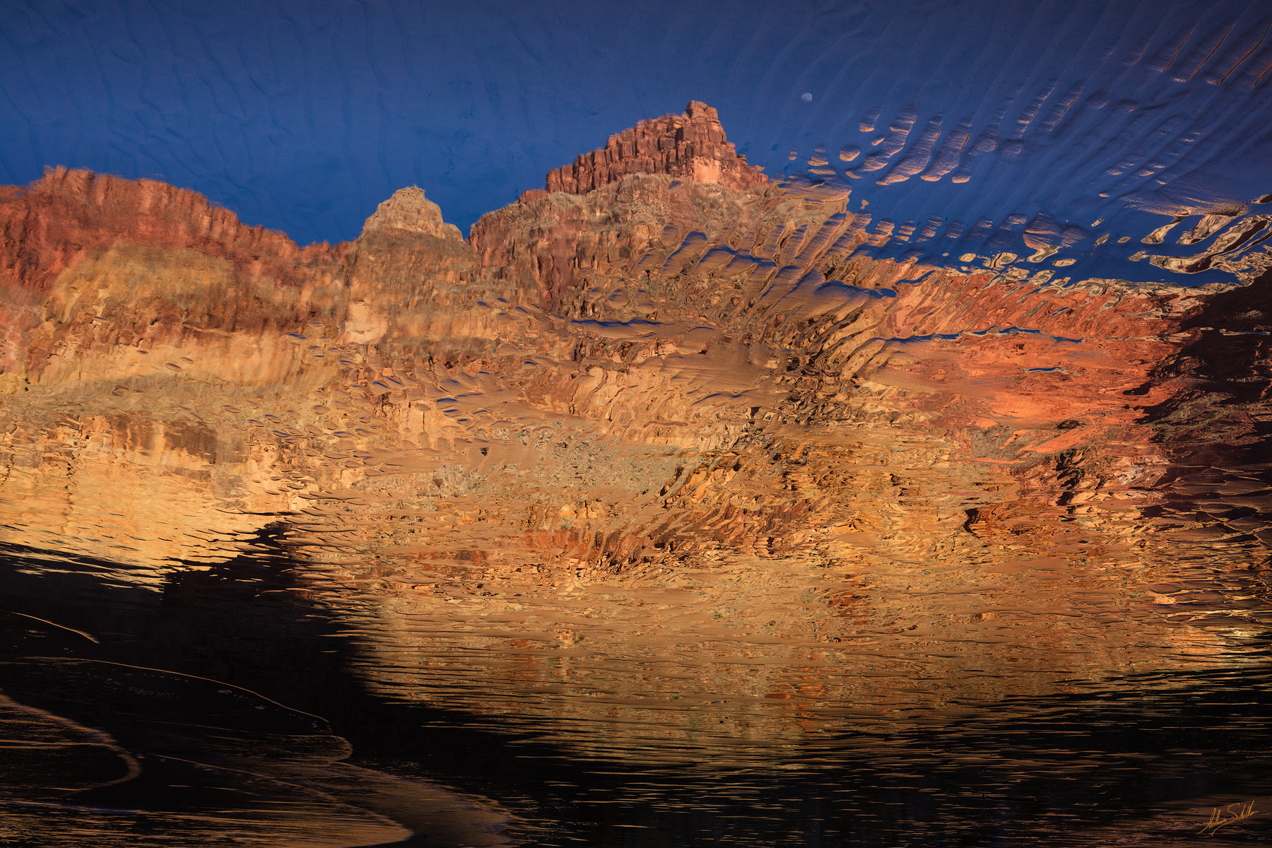Enfilade Point and the setting moon are refeclted in the waters of the Colorado River in Grand Canyon National Park. This photo...