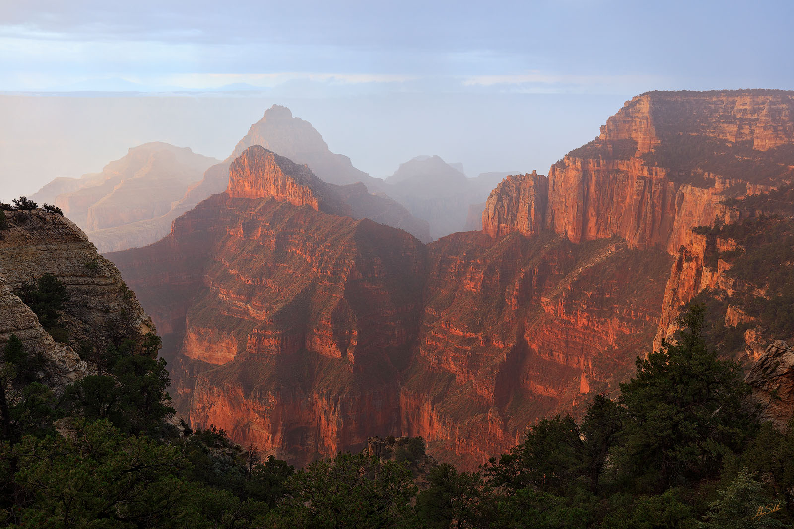 A light rain falls into the Grand Canyon just as the sun rises. The warm glow of the early morning light glows within a massive...