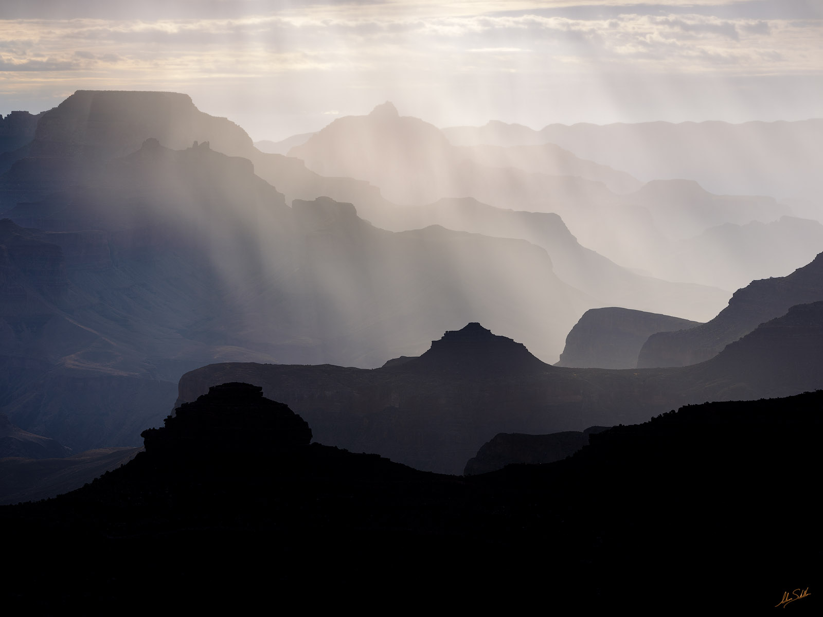 A gentle rain silently falls into Grand Canyon just after sunrise creating a beautiful atmosphere and accentuating the many ridges...