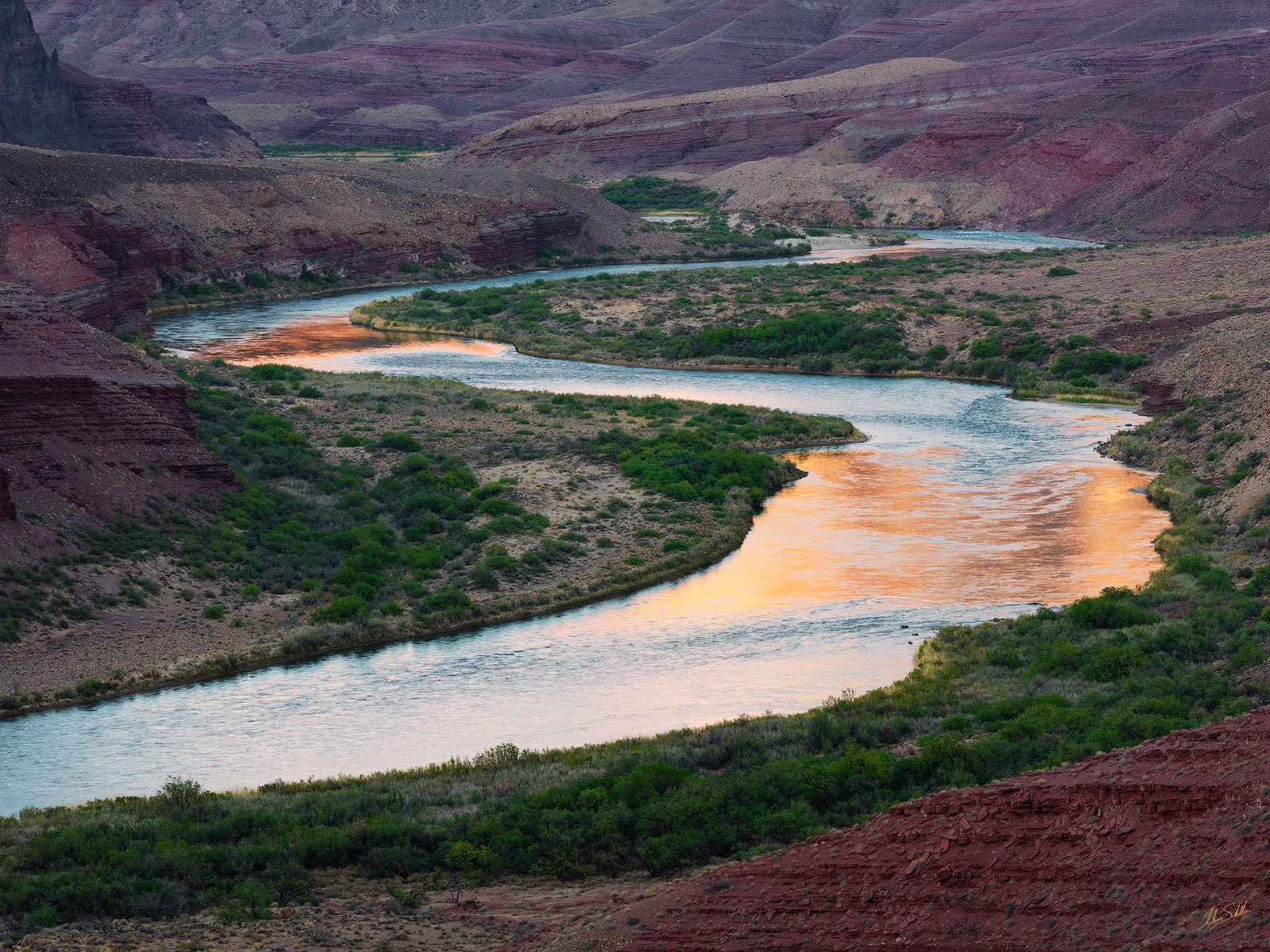 The warm light of sunset on distant cliffs reflects in the Colorado River. From the Escalante Route in Grand Canyon National...