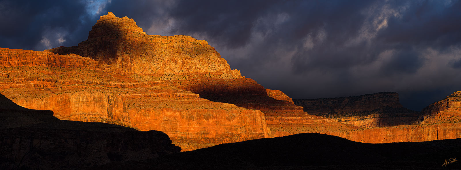 Storm clouds move across Vishnu Temple and the North Rim as the first rays of light of a new day paint the cliffs in fiery hues...