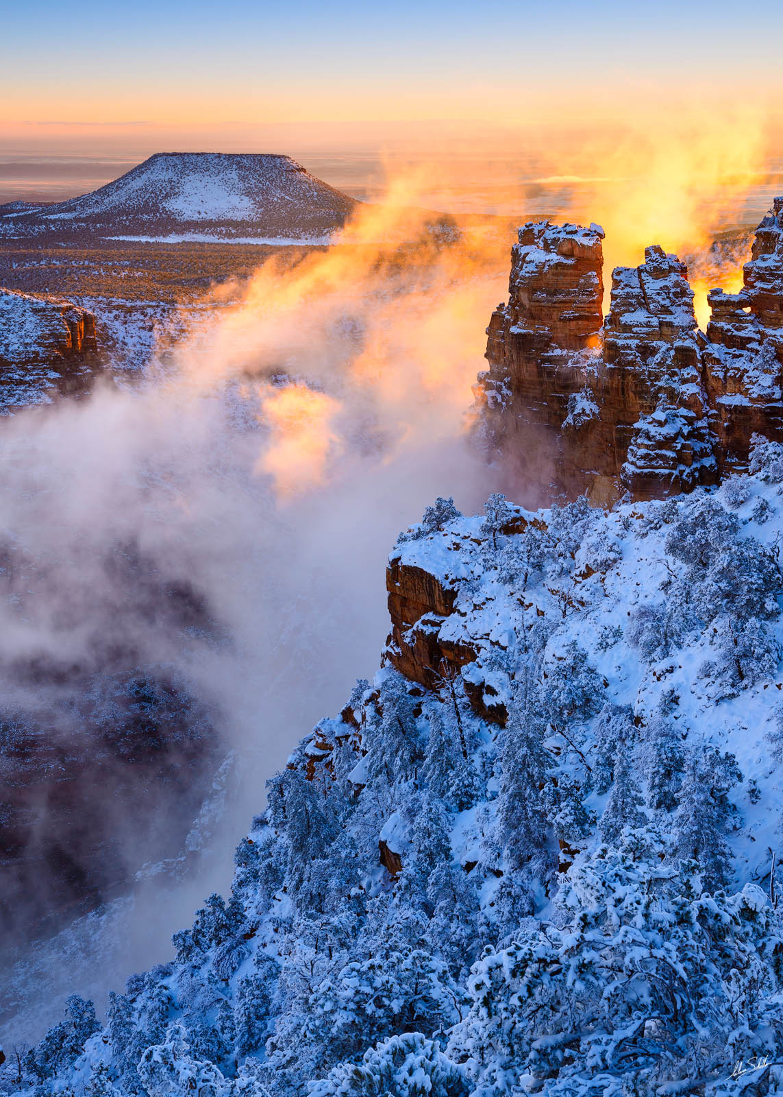 Clouds rise out of the Grand Canyon after a winter storm leaves behind a fresh blanket of snow. In the distance is Cedar Mountain...