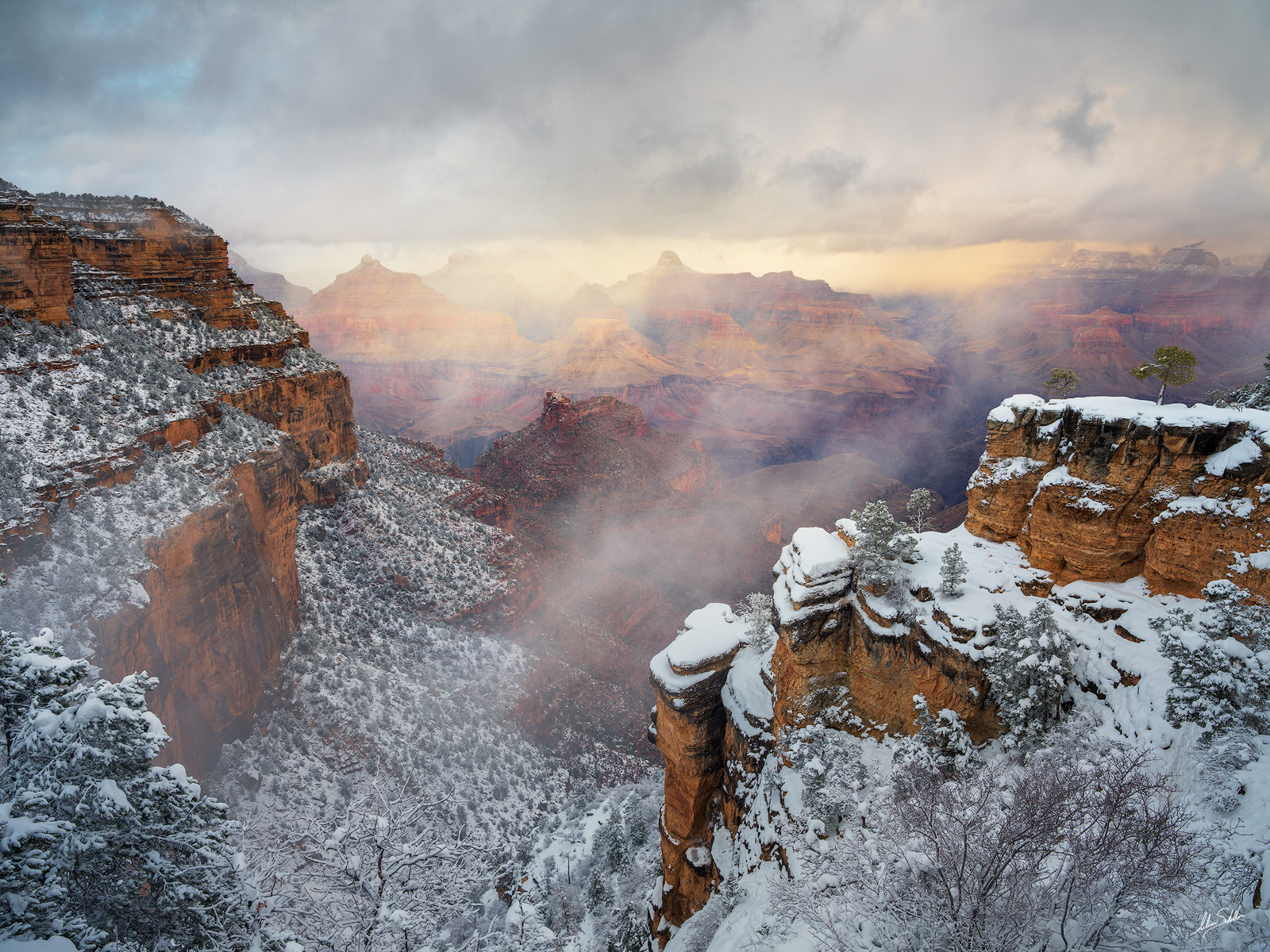 A winter storm closes in upon the Grand Canyon. Clouds begin to form within the depths of the canyon as snow falls on the distant...
