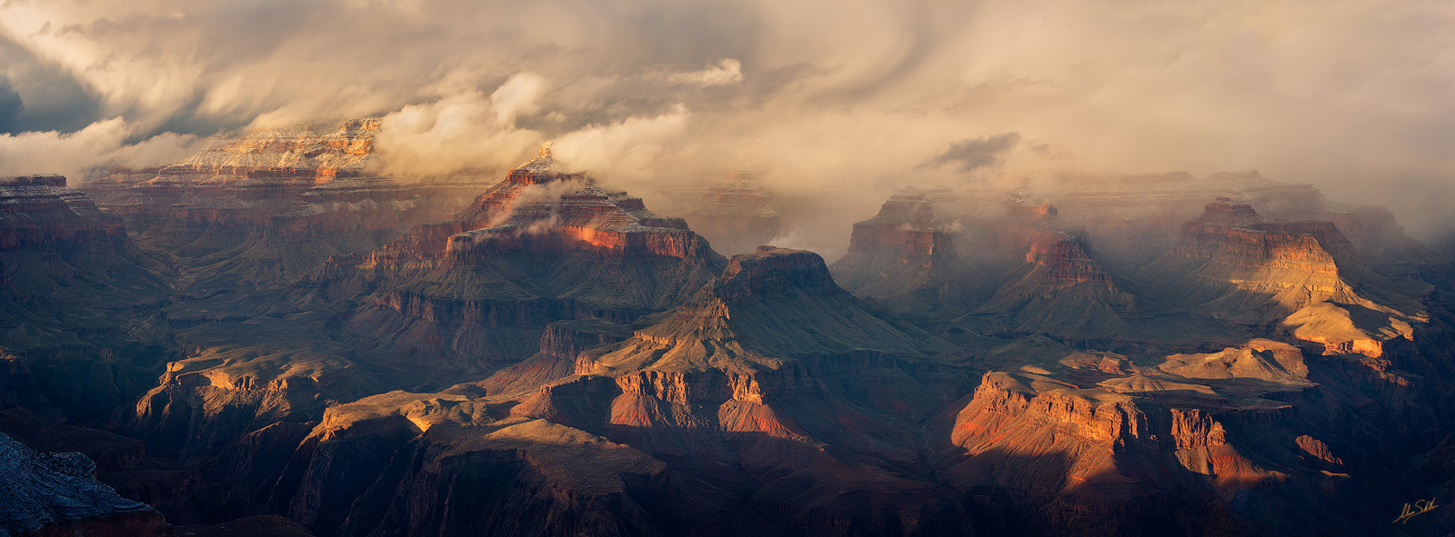 Dramatic light falls upon the Grand Canyon as the clouds from a winter storm are shredded by the landscape. Isis Temple appears...